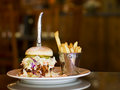 Pulled pork and cole slaw sandwich photo of huge with knife bucket of garlic french fries on white plate with blurred background Royalty Free Stock Image