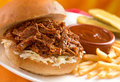 Pulled pork sandwich a delicious with barbecued shoulder coleslaw french fries dipping sauce and pickles Stock Photo
