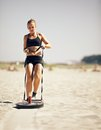 Pulling a crossfit sled woman across beach Royalty Free Stock Image