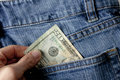 Pulling out money from rear pocket a person a twenty dollar bill of a denim blue jean back Stock Image