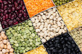 Pulses food background, assortment  - legume, kidney beans, peas, lentils in square cells closeup top view. Royalty Free Stock Photo