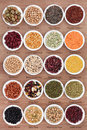 Pulses large dried selection with titles in white porcelain dishes over papyrus background Stock Photo