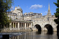 Pulteney bridge and the river avon in bath st michael s church can be seen in background Royalty Free Stock Images