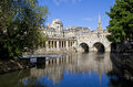 Pulteney bridge and the river avon in bath st michael s church can be seen in background Royalty Free Stock Photography
