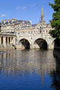 Pulteney bridge and the river avon in bath st michael s church can be seen in background Royalty Free Stock Photo