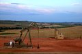 Pump Jack with Fields and Flares in Background Royalty Free Stock Photo