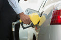 Pumping gasoline fuel at gas station close up of man in car Stock Photos