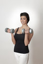 Pumping muscles portrait of young asian female doing exercises with dumbbells Royalty Free Stock Photography