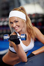 Pumping up biceps smiling athletic woman in a gym Royalty Free Stock Photo