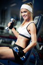 Pumping up biceps smiling athletic woman in a gym Stock Photography