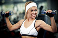 Pumping up biceps smiling athletic woman in a gym Stock Images
