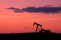 Pumpjack at sunset an oil silhoutted in a colorful Stock Images