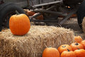Pumpkin on bale of straw a single halloween carving with additional pumpkins in foreground and old farm wagon blurred in Stock Image