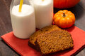 Pumpkin bread close up of slices of pecan sitting on orange cloth napkin with glasses of milk Stock Photos