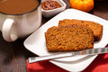 Pumpkin bread cup of fresh brewed coffee with slices of sitting on white plate Stock Images