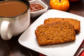 Pumpkin bread large cup of coffee with slices of pecan sitting on white plate with container of butter Royalty Free Stock Images