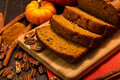 Pumpkin bread sliced loaf of pecan cinnamon sitting on wooden cutting board with orange napkin Stock Image
