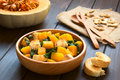 Pumpkin and chard salad with croutons served in wooden bowl photographed on dark wood with natural light selective focus focus in Stock Image