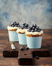 Pumpkin cupcakes decorated with cream cheese frosting and fresh blueberries copy space on a wooden background Stock Photo