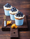 Pumpkin cupcakes decorated with cream cheese frosting and fresh blueberries on a wooden background copy space Royalty Free Stock Photo