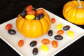 Pumpkin filled with halloween jellybeans mini on a white plate Royalty Free Stock Images