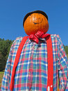 Pumpkin headed scarecrow a with a bright colored plaid shirt neckerchief and suspenders Stock Photography