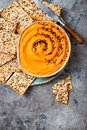 Pumpkin hummus seasoned with olive oil and black sesame seeds with whole grain crackers. Healthy vegetarian appetizer or snack.