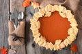 Pumpkin pie with autumn leaf pastry design, overhead table scene