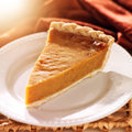 Pumpkin pie basked in warm light close up photo of a single piece of with lens flare Stock Photo