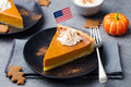 Pumpkin pie, tart made for Thanksgiving day with whipped cream with American flag on top. Royalty Free Stock Photo