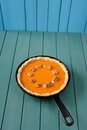 Pumpkin pie with wallnuts in cast iron skillet on turquoise wood