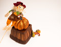 Pumpkin posing a small scarecrow leans on his large in this still life Stock Photography
