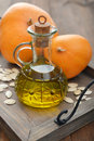 Pumpkin seed oil in bottle with seeds and on wooden background Stock Photo