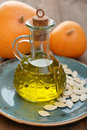 Pumpkin seed oil in bottle with seeds and on wooden background Stock Images