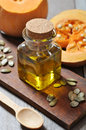 Pumpkin seed oil in glass bottle on rustic wooden background Stock Photo