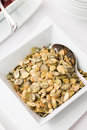 Pumpkin seeds in ceramic bowl on table Royalty Free Stock Photo