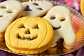 Pumpkin shaped and ghost shaped cookies closeup of a golden tray with a cookie some other Royalty Free Stock Photo