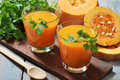 Pumpkin smoothie in glass on rustic wooden background Stock Images