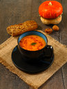 Pumpkin soup bowl of with bread on rustic table Royalty Free Stock Photos