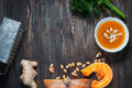 Pumpkin soup in a bowl with fresh pumpkins, ginger and parsley herbs
