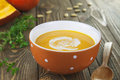 Pumpkin soup bowl of on a wooden table Royalty Free Stock Image