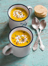 Pumpkin soup in ceramic mugs on a wooden surface healthy food Royalty Free Stock Photos