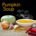 Pumpkin soup concept with its ingredients on a rustic plank background with real steam rising and space for text Stock Image