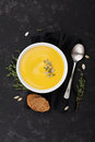 Pumpkin soup decorated seeds and thyme in white bowl on black table top view. Flat lay styling. Royalty Free Stock Photo