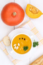 Pumpkin soup with fresh pumpkins in bowl from above