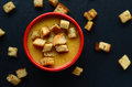 Pumpkin soup with homemade croutons in a small, red bowl Royalty Free Stock Photo