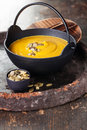 Pumpkin soup with seeds in a black iron pot Stock Image