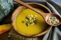 Pumpkin soup in a wooden bowl with fresh pumpkins