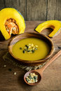 Pumpkin soup in a wooden bowl with fresh pumpkins on wooden tabl