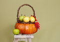 Pumpkins and apples in baskets on wood bench weave orange decorated with flowers fall leaves rustic againt light green Royalty Free Stock Images